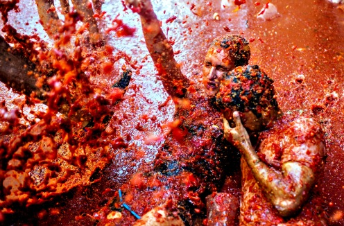 The World's Biggest Tomato Fight At Tomatina Festival...BUNOL, SPAIN - AUGUST 26: Revellers enjoy the atmosphere in tomato pulp while participating the annual Tomatina festival on August 26, 2015 in Bunol, Spain. An estimated 22,000 people threw 150 tons of ripe tomatoes in the world's biggest tomato fight held annually in this Spanish Mediterranean town. (Photo by David Ramos/Getty Images)